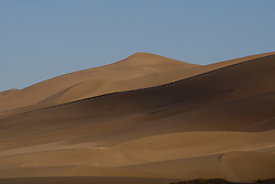 The dune field in early morning.  Great Sand Dunes National Park and Preserve contains the tallest sand dunes in North America. The Dunefield, topping off with Star Dune at 750 feet, is created by sand trapped by the nearby Sangre de Christo Mountains (larger rougher grains and pebbles) and the San Juan Mountains (65 miles to the west).  Waterways such as Medano Creek help carry the sediment down to the San Luis valley where the dunes are found. Great Sand Dunes National Park and Preserve, Mosca, Colorado.