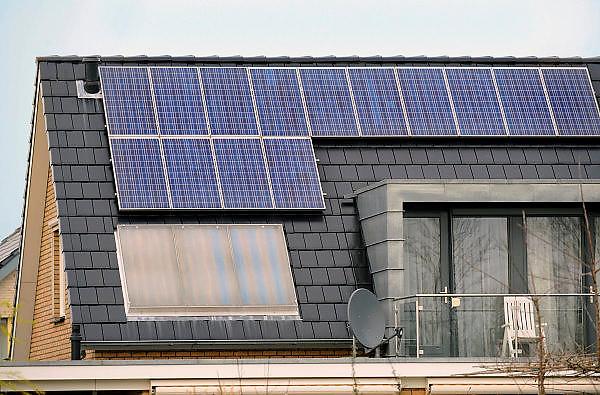 Nederland, Huissen, 15-3-2008..Een huis met zonnepanelen en een zonnecollector op het dak. de elekriciteit die de zonnecellen produceren voorzien in de helft van het stroomverbruik van dit huishouden. De warmtecollector geeft warm water van april tot oktober. Het kabinet, de regering heeft weer subsidie beschikbaar gesteld voor deze vorm van energieopwekking voor partikulieren...Foto: Flip Franssen/Hollandse Hoogte