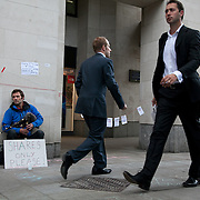 Day three of the occupation - and the first Monday. Many city workers make their way through the square to get to work. An activist is busking, playing to passers by asking for shares only. The square has been renamed Tahrir Square after the square in Cairo. The Occupy London Stock Exchange movement was formed in London in solidarity with the US based Occupy Wall Street. The movements are a respons and in anger to what is seen by many as corporate greed and a failed banking system being bailed out by the public, - which in return are suffering austerity measures to make up for the billions of lost money. The movement occupied the St Paul's Square in the City of London Sat Oct 15 after it failed to secure and occupy Pator Noster Square and the Stock Exchnage itself.