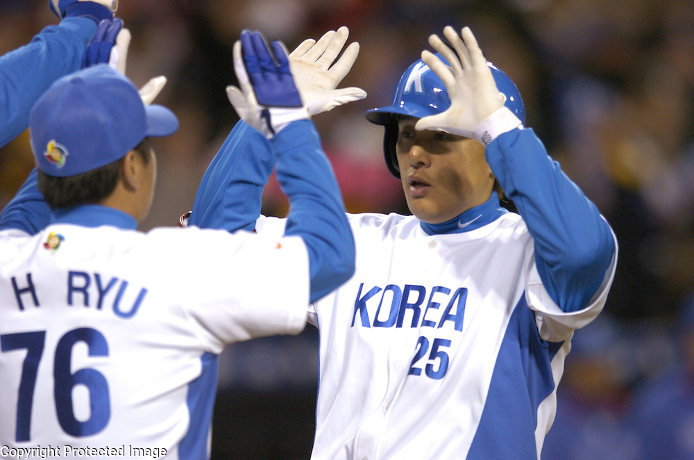 Team Korea's Seung Yeop Lee #25 is congratulated after his two-run home run against Team Mexico in Round 2 action at Angel Stadium of Anaheim.