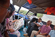 Commuters take the water taxi through the mangrove swamps from Bangar to Bandar, a lady reads an illustrated article about the Sultan of Brunei.