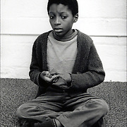 African American child withdrawn, sitting on floor, who is severely developmental disabled and autistic in private program in Bronx, NY
