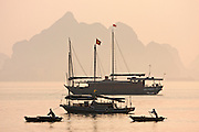 Halong Bay. Tourist and rowing boats at sunrise.
