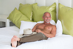 sexy middle aged man in a modern bed