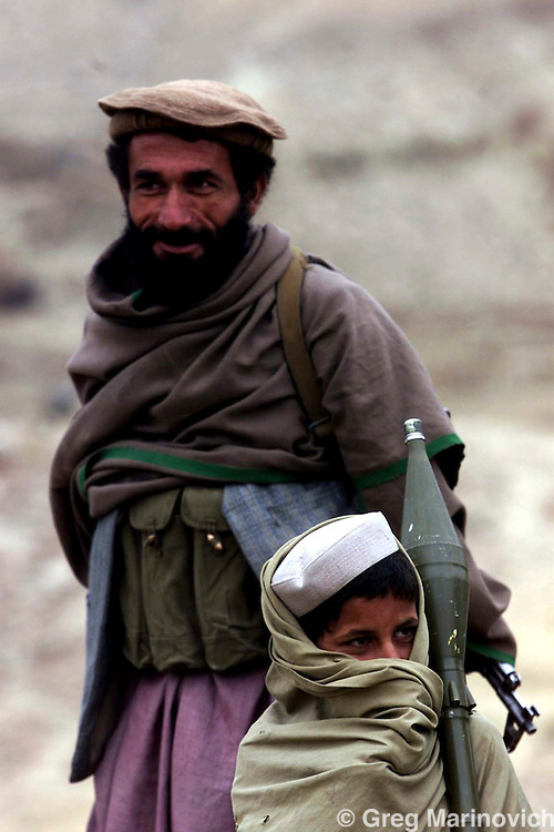 Afghanistan: Tora Bora: December 13, 2001:A young Afghan boy carries a rocket belonging to a Mujehadin near the Tora Bora front-line in Eastern Afghanistan. American planes today continued to drop bombs over Al Qaeda positions in the Tora Bora mountains. (Photo:Joao Silva/PictureNET Africa)
