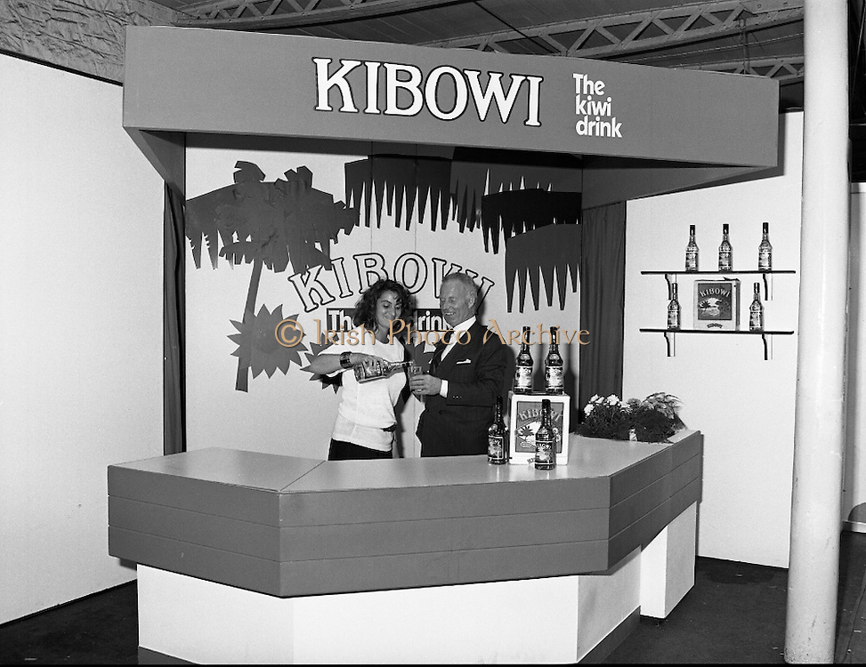 "The Dublin Horse Show   (R39)..1986..07.08.1986..08.07.1986..7th August 1986..At the Dublin Horse Show, Irish Distillers presented a new drink to the Irish marked. They displayed the drink 'Kibowi', the Kiwi drink on their specially commissioned stand. where passers by could sample it..Irish Distillers also sponsored a ""Drinks'"" evening for their invited guests at the hall in the RDS. the .Images show the ""Kibowi'' stand and the guests at the reception."