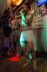 © Licensed to London News Pictures. 27/06/2015. Pilton, UK.  Night-time festival atmosphere at Glastonbury Festival 2015 in the Shangri-La area of the festival - a festival goer strips to his underwear on stage at the Kamikaze Karaoke bar, egged on by a male performer in drag with fake breasts.  On Saturday Day 4 of the festival.  Shangri-La is a destroyed dystopian pleasure city.  This years headline acts include Kanye West, The Who and Florence and the Machine, the latter being upgraded in the bill to replace original headline act Foo Fighters. Photo credit: Richard Isaac/LNP