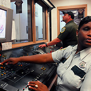African American Female Detention Service Officer (#1989) and Correction Office in background (#1990), Security of the Doors, main control room at the female Detention Center. Duty is in control room , maintaining security of the facility by monitoring cameras and opening and closing security doors