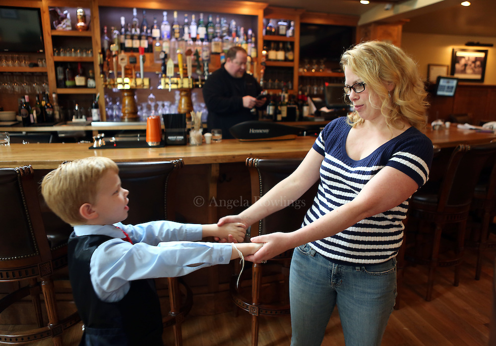 (Falmouth, MA - 5/28/15) Charlie Rickard, 8, who works weekends as a maitre d' in his parents' Falmouth restaurant, Bear in Boots, shares a moment with his mom, Kate, during downtime at the restaurant, Thursday, May 28, 2015. He says he is better on the computer than his mom, so he is able to update the tables quickly, and he enjoys talking with people. Staff photo by Angela Rowlings.