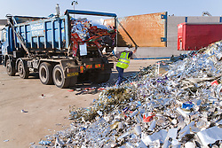 Tipper lorry which has picked up discarded tin cans from factories arriving at metal recycling centre and whose contents will be put in a pile for sorting,