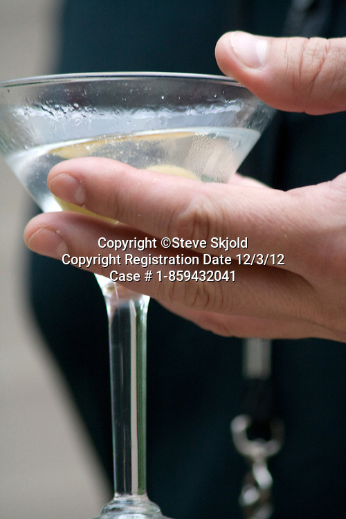 Man age 35 holding martini alcohol drink in a stemmed glass. St Paul Minnesota MN USA