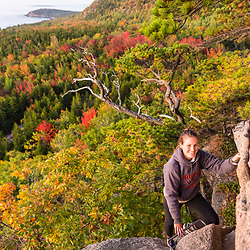 "A woman hiking ""The Beehive"" in fall in Maine's Acadia National Park."
