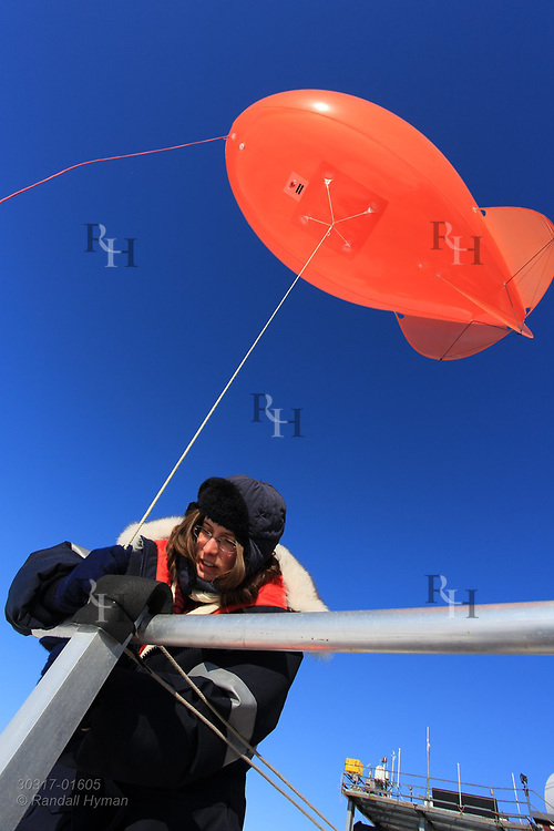 Woman scientist launches tethered weather blimp at the French-German AWIPEV research station in the international science village of Ny-Alesund on Spitsbergen island in Kongsfjorden; Svalbard, Norway.
