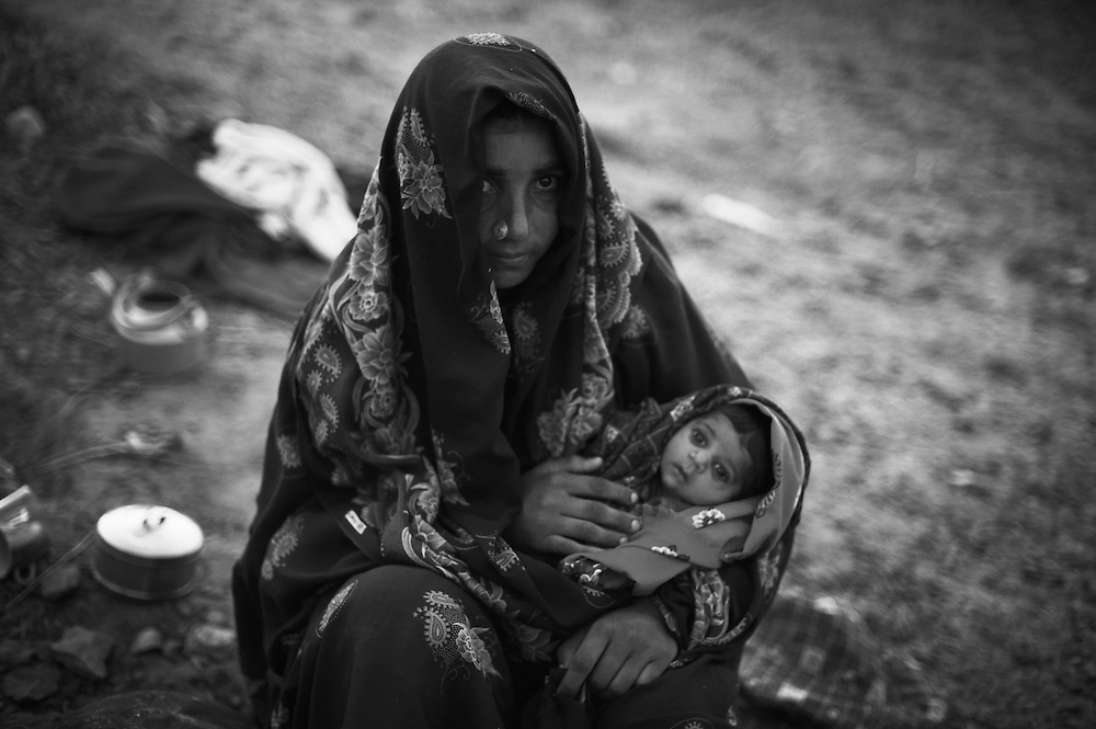 Gulzadi, 25 years old, an ethnic Balochi woman from Sanghar, sits with her baby in a UNHCR emergency relief camp for flood affected communities alongside a road between the city of Hyderabad and Thatta, Thatta District, Sindh, Pakistan on September 28, 2011. The baby suffers from constipation due to drinking contaminated rain water. A community of 35 ethnic Balochi families traveled to this UNHCR site on trucks, from Sanghar in Sindh province, a distance of 150 kilometres away, a journey of seven hours. Their homes and crops where washed away after heavy rains flooded them in August 2011. They also lost livestock but have traveled to this site with what they could, including their goats. There is a shortage of clean water at the site. The contamination in the rain water they collect from a site 3 kilometres away has resulted in constipation, malaria and skin problems. They have lost everything and envision returning home in 4-5 months. Heavy monsoon rains triggered flooding in lower parts of Sindh and northern parts of Punjab. To date, the Government of Pakistan reports that more than 5.3 million people have been affected, Over 300 people have lost their lives, over 4.2 million acres of land flooded and 1.59 million acres of crops destroyed. UNHCR is supplying 10,000 tents, 20,000 plastic sheets and 10,000 kits of household items as an emergency response to flood affected communities in Sindh Province. Contingent on an emergency funding appeal, UNHCR will be able to supply another 20,000 tents and relief items. Thatta District, Sindh, Pakistan on September 28, 2011.