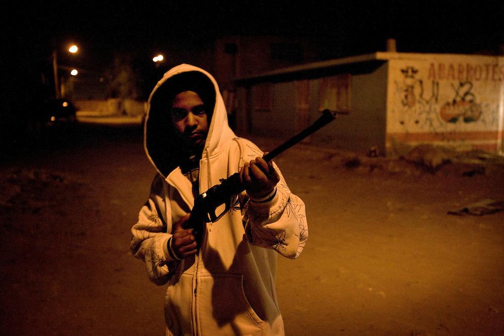 Members of  Juarez's Baja 13 gang show off their tattoos and guns, Saturday, April 4, 2009