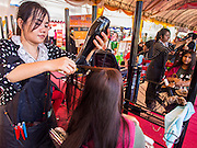 "24 JULY 2014 - BANGKOK, THAILAND:  A woman gets her hair done for free at the happiness party in Bangkok. The Thai Junta is organizing a series of public events throughout Thailand meant to bolster public opinion. The events are called ""restoring happiness to the people"" parties. They feature historic pageants, music, food, health checks and free haircuts. The party in Bangkok is on Sanam Luang, the Royal Parade Ground, which is near the Grand Palace and the Ministry of Defense.   PHOTO BY JACK KURTZ"