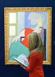 """© Licensed to London News Pictures. 31/01/2013. London, UK An employee holds a catalogue in front of Pablo Picasso's """"Femme assize press dune fenetre"""" 1932 which is estimated to raise 25-35million GBP. Preview of highlights from Sotheby's forthcoming February sales of Impressionist & Modern Art and Contemporary Art in London, including works by Picasso, Bacon, Monet, Richter and Miró. Photo credit : Stephen Simpson/LNP"""