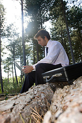 Young businessman sitting on a tree trunk using a laptop computer