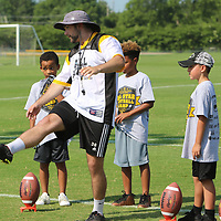 Drew White teaches kids the proper way to kick a football Saturday at the All-Star Football Camp benefiting the Boys and Girls Clubs of North Mississippi
