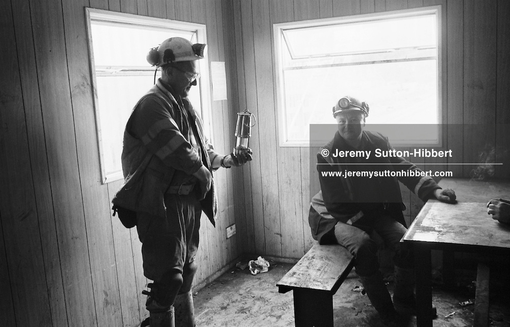 MINERS WAITING TO BOARD THE TROLLEY TRAIN WHICH WILL TAKE THEM UNDERGROUND TO START THEIR TEN HOURS SHIFT AT LONGANNET COLLIERY, NEAR CULROSS. SCOTLAND, APRIL, 2001...©JEREMY SUTTON-HIBBERT 2001...