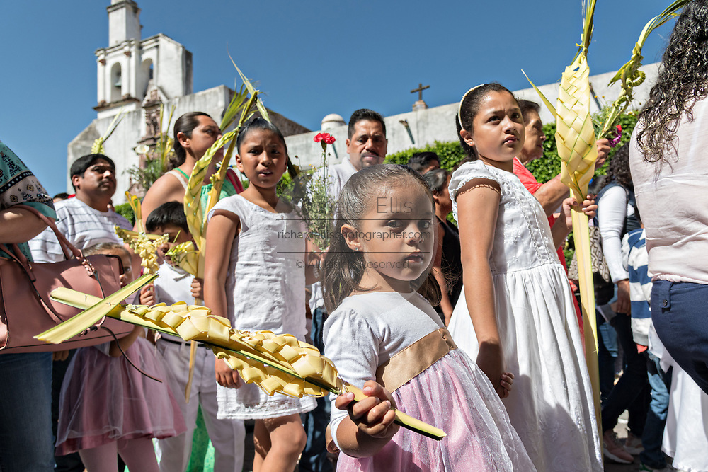 Young believers carry woven palm crosses during a Palm Sunday procession through the streets at the start of Holy Week March 25, 2018 in San Miguel de Allende, Mexico. Christians commemorate the entry of Jesus into Jerusalem when it was believed that the citizens laid down palm branches in his path.