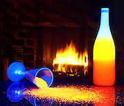 A glass of glowing crystals spilled on a table alongside a glowing bottle of wine with a fireplace in the background.Black light