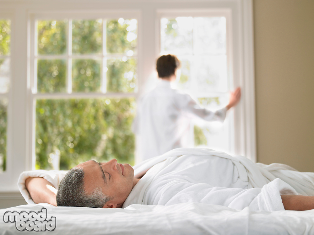Man relaxing in bed wife looking through window in background