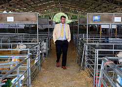 © Licensed to London News Pictures.16/07/15<br /> Harrogate, UK. <br /> <br /> A man walks through the sheep sheds on the final day of the Great Yorkshire Show.  <br /> <br /> England's premier agricultural show has seen three days of showcasing the best in British farming and celebrating the countryside.<br /> <br /> The event which attracts over 130,000 visitors each year displays the cream of the country's livestock and offers numerous displays and events giving the chance for visitors to see many different countryside activities.<br /> <br /> Photo credit : Ian Forsyth/LNP