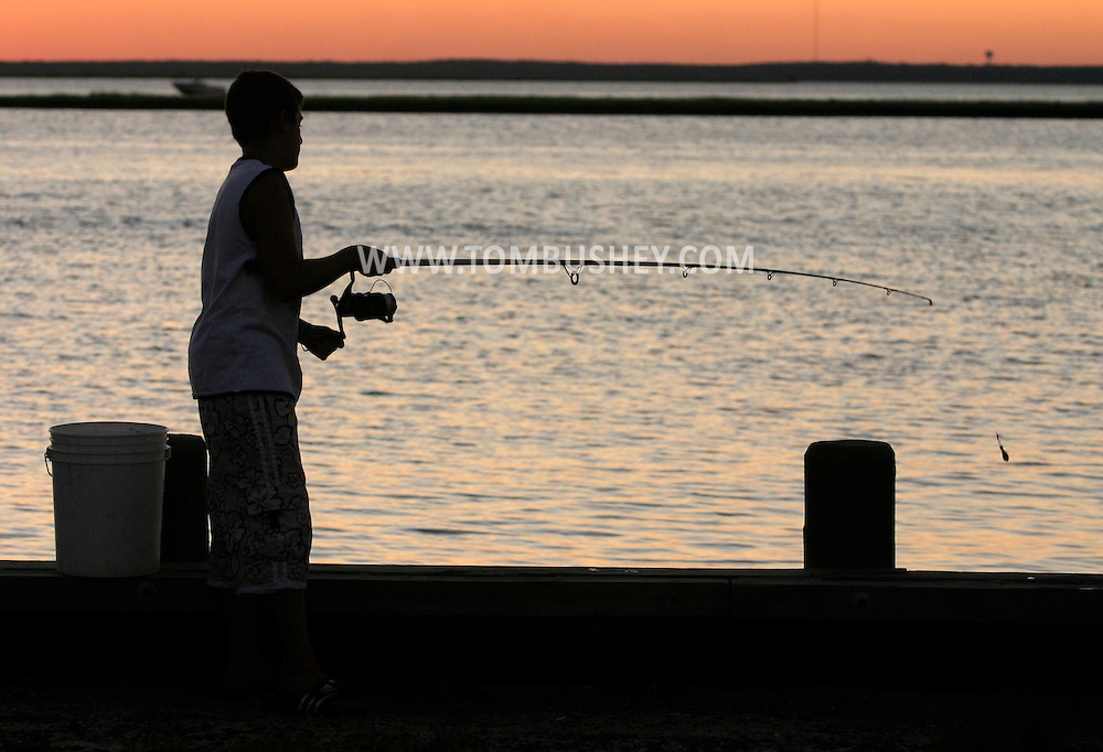 A boy fishes from the dock at sunset on Barnegat Bay at Spray Beach on Long Beach Island, N.J..Aug. 23, 2005........