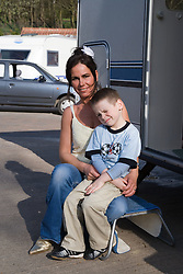 Mother and son sitting outside their caravan in the sunshine,