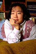 Korean woman age 29 thinking with hand on chin.  St Paul Minnesota USA