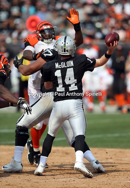 Oakland Raiders quarterback Matt McGloin (14) throws a third quarter pass under pressure from the outstretched hand and arm of a defender during the 2015 NFL week 1 regular season football game against the Cincinnati Bengals on Sunday, Sept. 13, 2015 in Oakland, Calif. The Bengals won the game 33-13. (©Paul Anthony Spinelli)