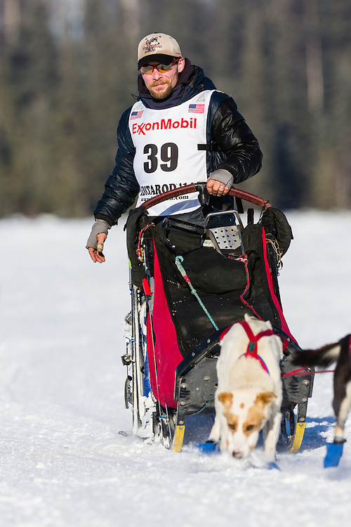 Musher Jason Mackey competing in the 42nd Iditarod Trail Sled Dog Race on Long Lake after leaving the restart on Willow Lake in Southcentral Alaska.  Afternoon. Winter.