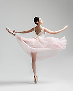 Classical female ballet dancer, Hwei Shin, in a pink romantic tutu in the photo studio on a grey background. Photograph taken in New York City by photographer Rachel Neville.