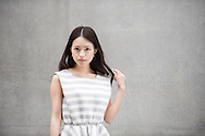 Portrait of a young fashionable Japanese woman. Beautiful Asian female in 20's looking to camera with grey concrete background.
