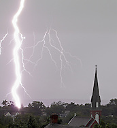Middletown, New York - Lightning strikes in the distance behind the steeple of St. Joseph's Church during a thunderstorm on July 26, 2012.