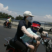 A decade ago Vietnams roads were teaming with bicycles. But as the countries economic growth increased bringing relative affluence to the working class, the push bike has been replaced by the scooter as the main mode of transport for the nations population.. Ho Chi Minh City alone has an estimated three million scooters buzzing around the streets day and night. Everyday life is dominated by the site of the scooter. Street corners have become parking lots for rows upon rows of parked scooters.. Puncture repair workmen wait on every city street to come to the aid of the rider with a blown tyre, and make a quick buck in the process, while families have a night on the town together, all seated on the same scooter!.Any number of items can be seen transported on the back of a scooter, from pigs to wardrobes anything that can be tied down is moved on the trusted scooter..Even in the outlying country areas the scooter is now used to transport produce to and from the markets. While even beach goers at the coastal towns head for a swim and a sunbathe accompanied by their scooter. .Scooters on the street of Nha Trang, Vietnam on September 29, 2006. Photo Tim Clayton