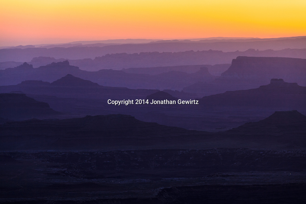 The brightening morning sky silhouettes distant ridges beyond Buck Canyon and the White Rim mesa in Canyonlands National Park, Utah.<br /> <br /> WATERMARKS WILL NOT APPEAR ON PRINTS OR LICENSED IMAGES.<br /> <br /> Licensing: https://tandemstock.com/assets/29754121