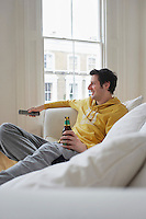 Man sitting on sofa watching television and holding beer bottle