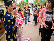 31 MARCH 2012 - HANOI, VIETNAM:  People look at a Vietnamese couple in formal wear outside of Ngoc Son Temple, which was reportedly built during the Tran Dynasty (ca 1225) in the Old Quarter of Hanoi, Vietnam. The temple is dedicated to Tran Hung Dao, a Vietnamese national hero who defeated an invading Mongol army in the 13th century.         PHOTO BY JACK KURTZ