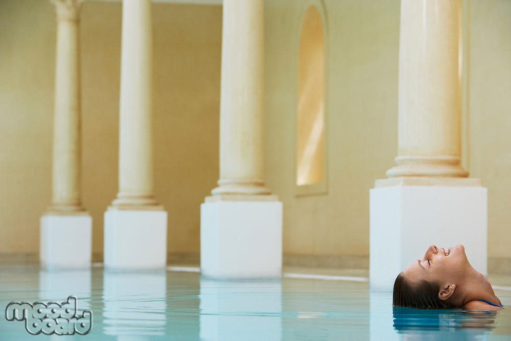 Smiling woman leaning backwards in swimming pool portrait