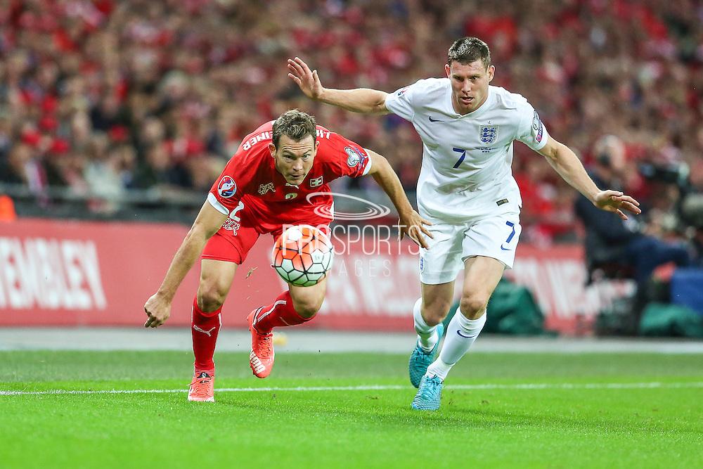 Switzerland's Stephan Lichsteiner and England's James Milner  during the UEFA European 2016 Qualifying match between England and Switzerland at Wembley Stadium, London, England on 8 September 2015. Photo by Shane Healey.