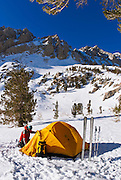Yellow dome tent and skier under Piute Pass, Inyo National Forest, Sierra Nevada Mountains, California