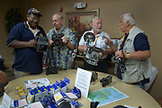 PENSACOLA, Fla. (Oct. 27, 2009) -- U.S. Navy photography veterans John Hudson, Stanley Toy, Ed Bailey and John Lewin gather around the camera display table where members of the National Association of Naval Photography (NANP) have met for a reunion in Pensacola Beach, Florida for a week long event of tours, meetings and awards banquet.  Photo by Johnny Bivera