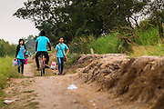 17 MARCH 2014 - BUNG KHAM PROI, PATHUM THANI, THAILAND:   Workers at a factory in Bung Kham Proi walk through a dried out rice field on their way to work. It hasn't rained in central Thailand in more than three months, impacting agriculture and domestic water use. Many farms are running short of irrigration water and salt water from the Gulf of Siam has come up the Chao Phraya River and infiltrated water plants in Pathum Thani province that serve Bangkok. PHOTO BY JACK KURTZ