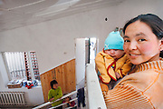 Shirin Aroonova (right) stands on the second floor landing to look at the work volunteers completed on 12 March 2006. Her children, in her arms is Isman (3-mos), on the stairs is Meerim (left, 12 yrs.) and IzLam (3 yrs.). When the home is reopened, her husband and family will be part of the staff and care takers of the children's home / physical therapy center. The Bishkek International Womens Club describes the home as being at the foot of the snow-decked mountains of the Tien-Shan range in the little village Kok Jar [.. over the o] (Schar) just outside Bishkek, Kyrgyz Republic, there used to be a small center where groups of handicapped children could receive therapeutic treatment over a periods of three weeks and where 8-10 homeless disabled children used to live. This center was part of the Hadjeshda Children?s Center, today housing more than 60 children and teenagers. However, in April 2004 the roof burned down and the other parts of the house were badly damaged.  Today more than 120 children are still waiting for the center to re-open. (U.S. Air Force photo by Master Sgt. Lance Cheung)<br />