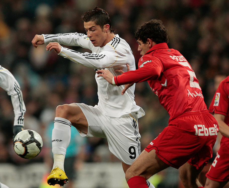 Real Madrid's Cristiano Ronaldo from Portugal, left, vies for the ball with Sevilla's Federico Fazio from Argentina, right, during a Spanish La Liga soccer match at the Santiago Bernabeu stadium, Saturday, March 6, 2010.