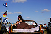 """A festival-goer relaxes in the back of a ute at the annual Deniliquin Ute Muster in Deniliquin, Australia. A """"ute"""" is a term used in Australia for a utility vehicle, popular in the rural areas and used for farming and other work needs."""