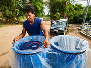 10 MAY 2016 - TA TUM, SURIN, THAILAND: A man covers his water barrels with plastic getting water from the artesian well in Ta Tum, Surin, Thailand. The well is the most important source of drinking water for thousands of people in the communities surrounding it.  In the past many of the people had domestic water piped to their homes or from wells in their villages but those water sources have dried up because of the drought in Thailand. Thailand is in the midst of its worst drought in more than 50 years. The government has asked farmers to delay planting their rice until the rains start, which is expected to be in June. The drought is expected to cut Thai rice production and limit exports of Thai rice. The drought, caused by a very strong El Nino weather pattern is cutting production in the world's top three rice exporting countries:  India, Thailand and Vietnam. Rice prices in markets in Thailand and neighboring Cambodia are starting to creep up.    PHOTO BY JACK KURTZ