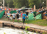 Paddlers from across Canada and the U.S. sprint to the river starting line of the 64th AuSable River Canoe Marathon.